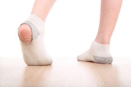 un cierre arriba de un pies de muchachos j�venes con orificios en sus calcetines