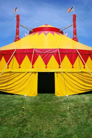 a close-up of a circus tent  on bright green grass and a blue sky