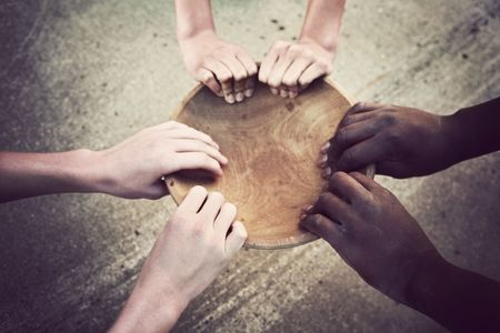 poor people: a multi-cultural group of hands holds an empty bowl Stock Photo