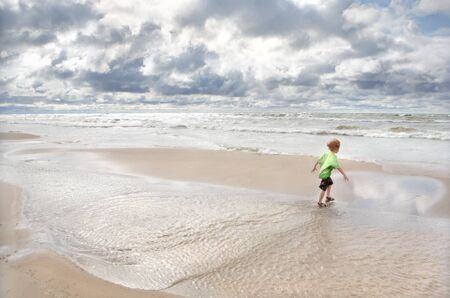 A young boy plays in the sand at the beach