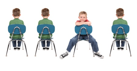 standout: A group of boys sit in school chairs. One is facing backwards and is wearing different clothes than the other boys. Stock Photo