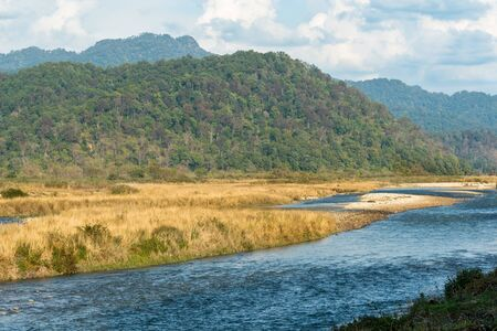 scenic landscape of Ramganga River with mountains and clouds in sky at dhikala zone of corbett national park or tiger reserve, uttarakhand, india