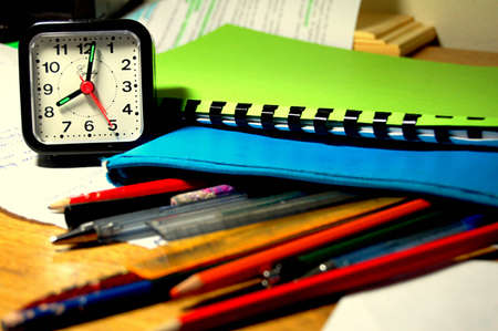 test deadline: Work desk with pencils, pens, papers and a clock. Stock Photo