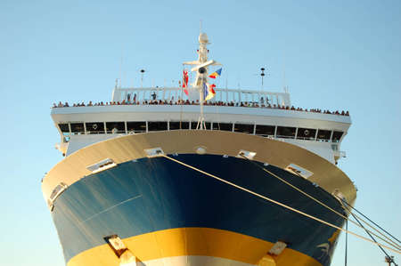 docked: Picture of a passenger ship docked, about to leave the wharf. Passengers can be seen at the front, waiting to say goodbye to friends and . Stock Photo