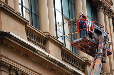 Two men cleaning windows while standing on a crane supported platform.