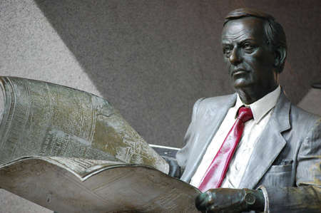 coporate: Waiting. Statue of a business person holding a newspaper. Statue located on Pitt street, sydney. Stock Photo