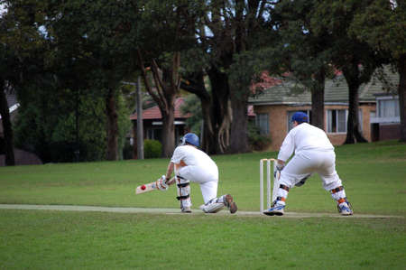 cricket game: A batsman plays the sweep shot in a game of cricket