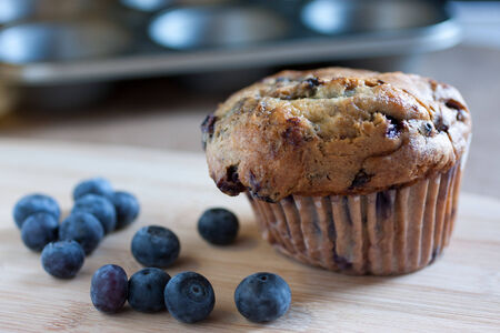 suface: A fresh blueberry muffin on a wooden suface wirh fresh  blueberries