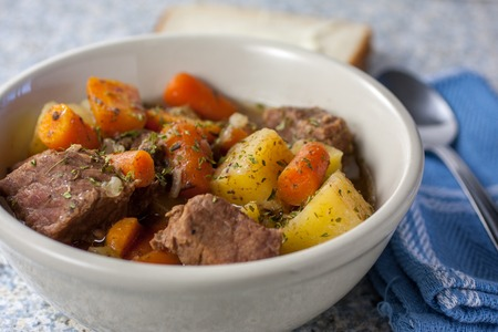 Fresh beef stew in a white bowl with carrots and potatoes.