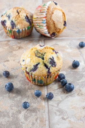 counter top: Blueberry muffins on  a tile counter top with fresh berries scattered around. Stock Photo