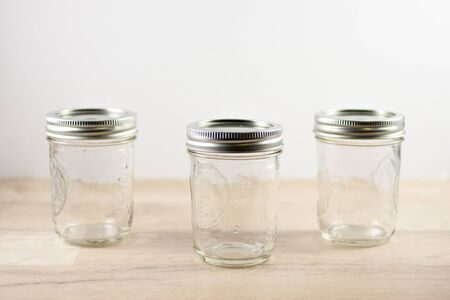 preperation: Empty canning jars await use on a wooden table.