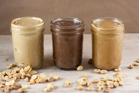 Peanut butter, hazlenut spread, and cashew butter on a wooden table.
