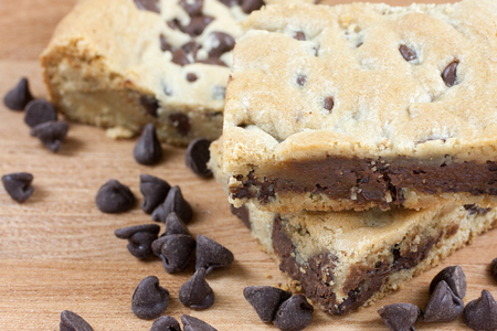 chocolate chip cookie: Chocolate chip cookie bars on a wooden surface with chocolate chips in the forground. Stock Photo