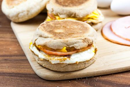 colazione: Focaccina inglese, uova, prosciutto, formaggio e panino prima colazione su un tagliere con ingredienti in background. Archivio Fotografico