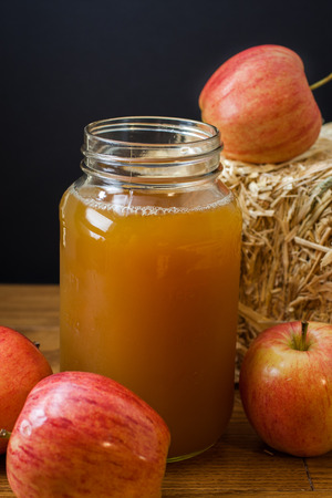 Fresh pressed apple cider and apples on a wooden table with a hay bale in the background.