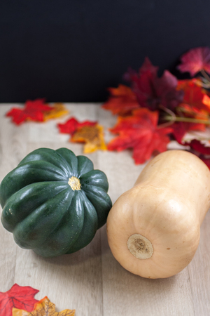 butternut squash: Acorn and Butternut squash on a table with fall leaves in the background. Stock Photo