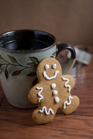A gingerbread man cookie and a cup of fresh coffee on a wooden table. photo