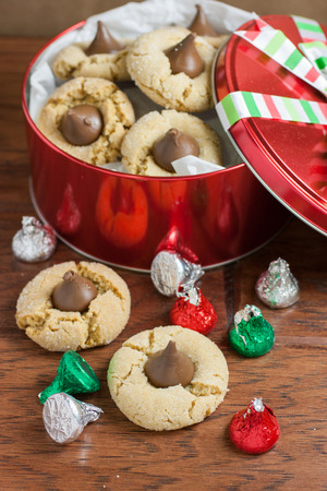 kiss biscuits: Preanut butter blossoms in a gift tin, highlighted with chocolate candies and and cookies on a wooden table.