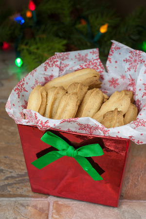 Piped spice cookies in a red gift box on a tile countertop.