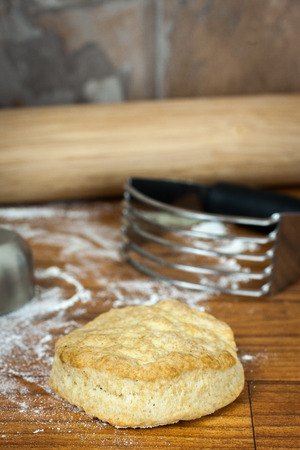 pastry cutter: A chrome pastry cutter sits on a counter top with rolling pin, butter, flour, and a biscuit on the background.