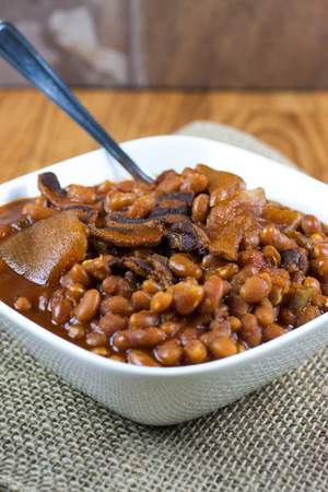 Rustic baked beans in a white bowl on a burlap placemat and wooden table. photo
