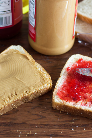 peanut butter and jelly sandwich: A peanut butter and jelly sandwich being constructed on a wooden table.
