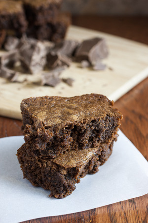 Chocolate brownies on a piece of parchment paper and chocolate chuncks on a cutting board in background. Stock Photo