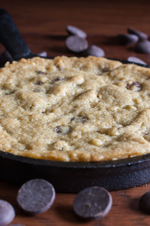 cast iron pan: A personal-sized chocolate chip cookie in a cast iron pan with chocolate chips in the background.