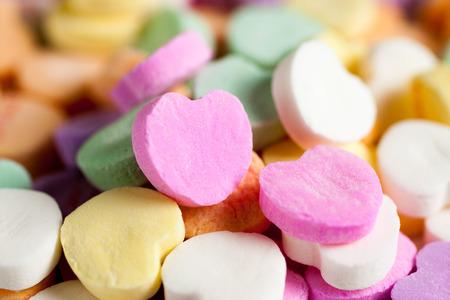 Pastel gekleurde snoep harten in een stapel op een witte ondergrond.