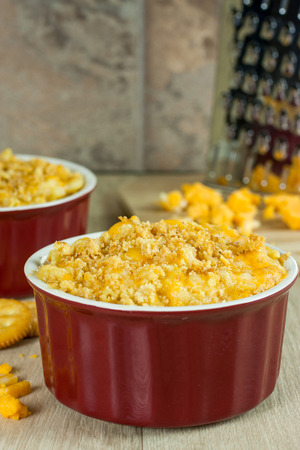 Baked macoroni and cheese topped with a crispy crust in red stone crocks with grated cheese in the background. Banco de Imagens