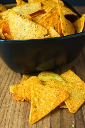 nacho: Nacho cheese flavored tortilla chips in a dark bowl on a wooden table.