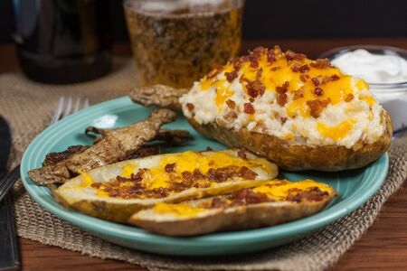 twice: A twice baked potato, potato skins, and baked potato peals with a beer and sour cream in the background.
