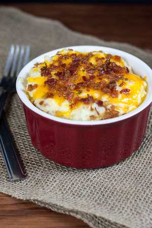A crock of loaded mashed potatoes with melted cheese and bacon on top.