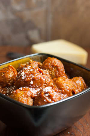 marinara: Itailian meatballs and marinara sauce in a bowl with a block of fresh Parmesan cheese in the background. Stock Photo