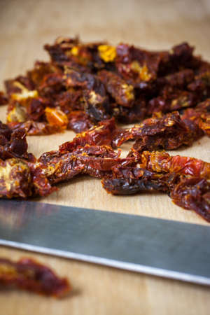 sun dried: Sun dried tomatoes sliced up on a wooden cutting board.