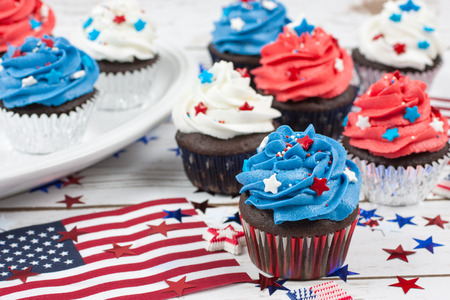 Chocolate cupcakes decorated in red, white, and blue and surrounded by stars and flags in celebration of  Independence Day.