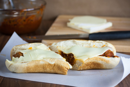 hoagie: A fresh meatball sandwich with cheese on parchment paper. Stock Photo