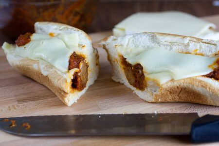 hoagie: A fresh meatball sandwich with cheese on wooden cutting board.