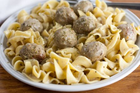 beef stroganoff: Beef stroganoff made with meatballs on a white plate and wooden table.