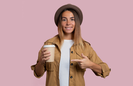 young girl on a pink background with a cup of coffee shows a finger on coffee Stock Photo