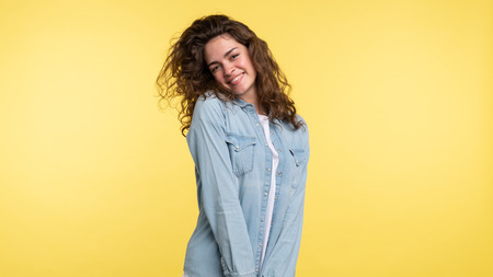 Pretty shuy brunette woman with curly hair isolated over yellow background