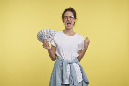 Young happy woman with curly hair holds a lots of cash and screaming of happiness, Stock Photo
