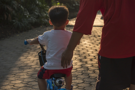 kid riding his bike along the paths of the park, dad supports his son, family