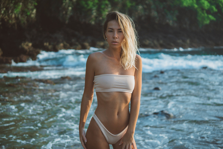 great sexy model with long legs standing in water, wears white stylish swimsuit,