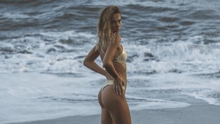 wonderful back shot of slim model in golden swimming suit posing on ocean beach,
