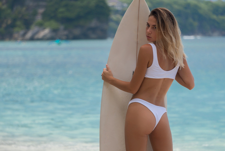magnificent view of back of slim girl in bikini with surf board in sunny day 스톡 콘텐츠