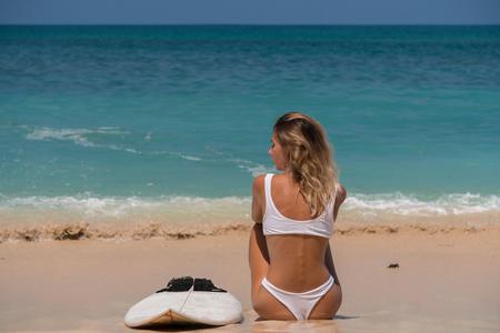 slender pretty blonde with surfboard facing to azure ocean, enjoys tropic sun,