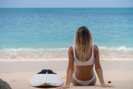 nice back view of wonderful girl sitting on pink sand beach with her surf board