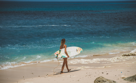 slim young surfer woman carries surfboard under her arm, walking on pink sand