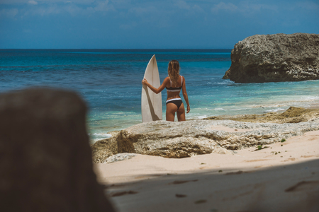 girl holding surfboard and watching ocean, magnificent views of pink sand beach